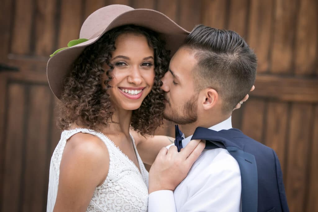 bride with brown hat and groom kissing her cheek