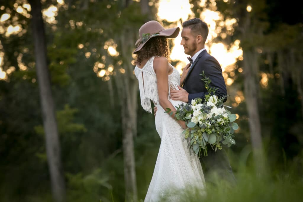 bride and groom with white flowers in woods