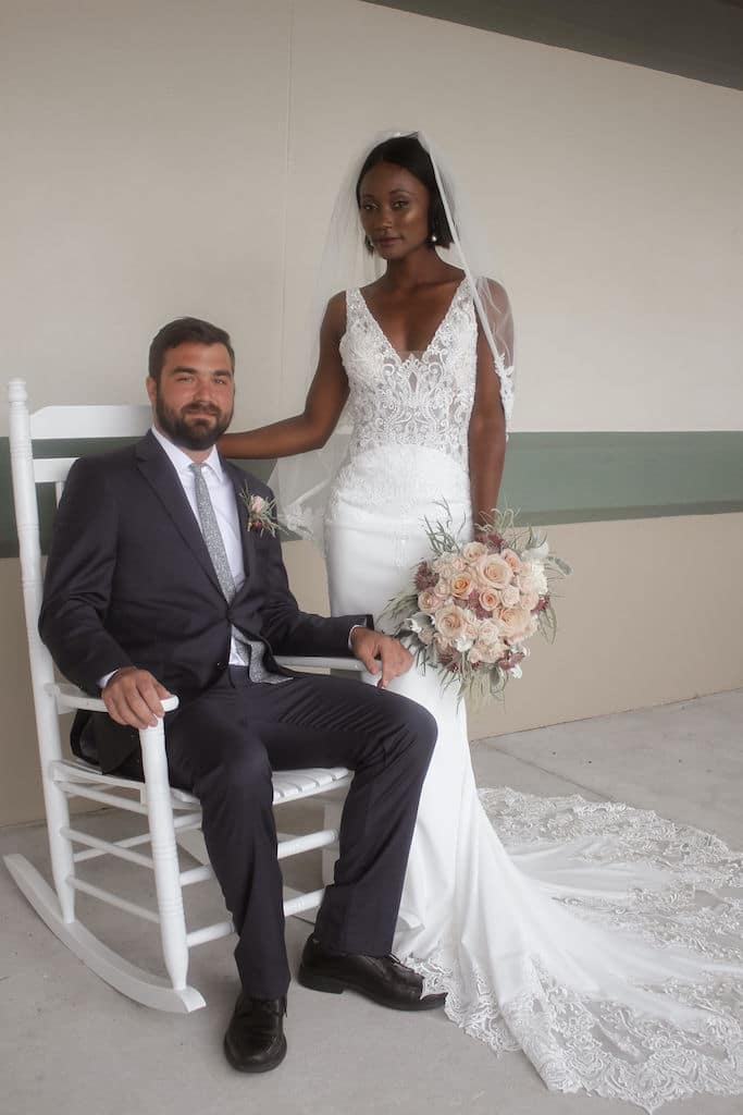 Barney E. Veal Center groom sitting on white rocking chair with bride standing next to him
