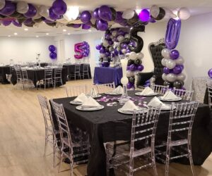 purple and black balloons with table setting