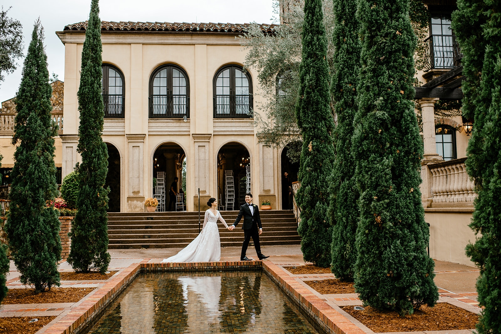 bride and groom walking outside by water and trees