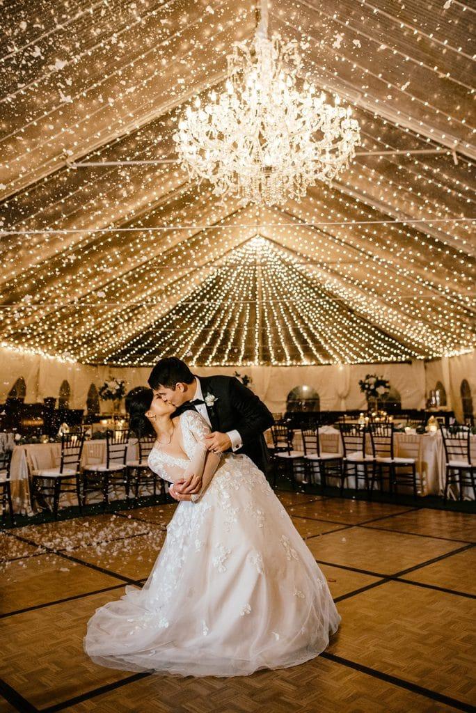 Bella Collina, bride and groom kissing on dance floor under lights and chandelier