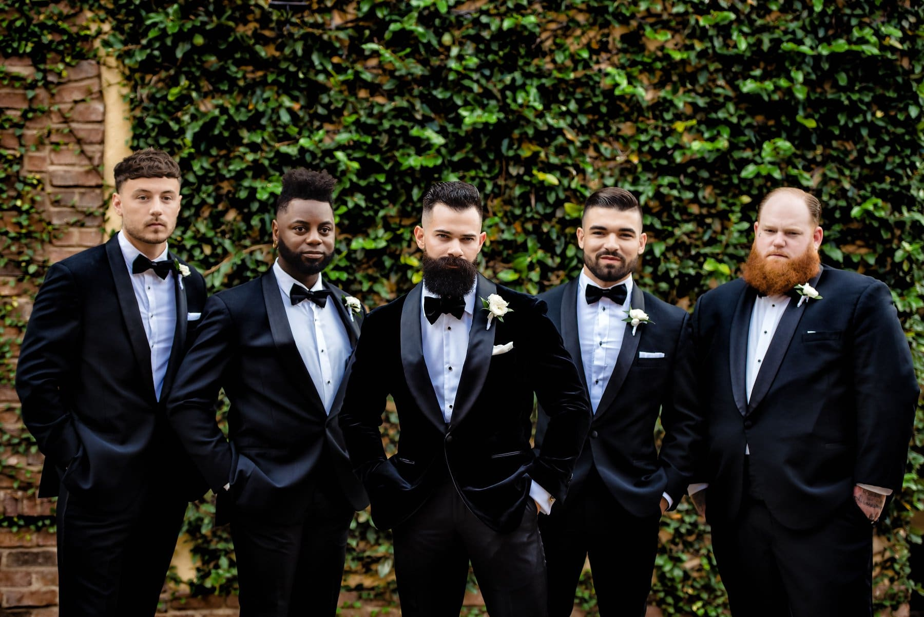 groomsmen standing in front of brick wall covered in vines