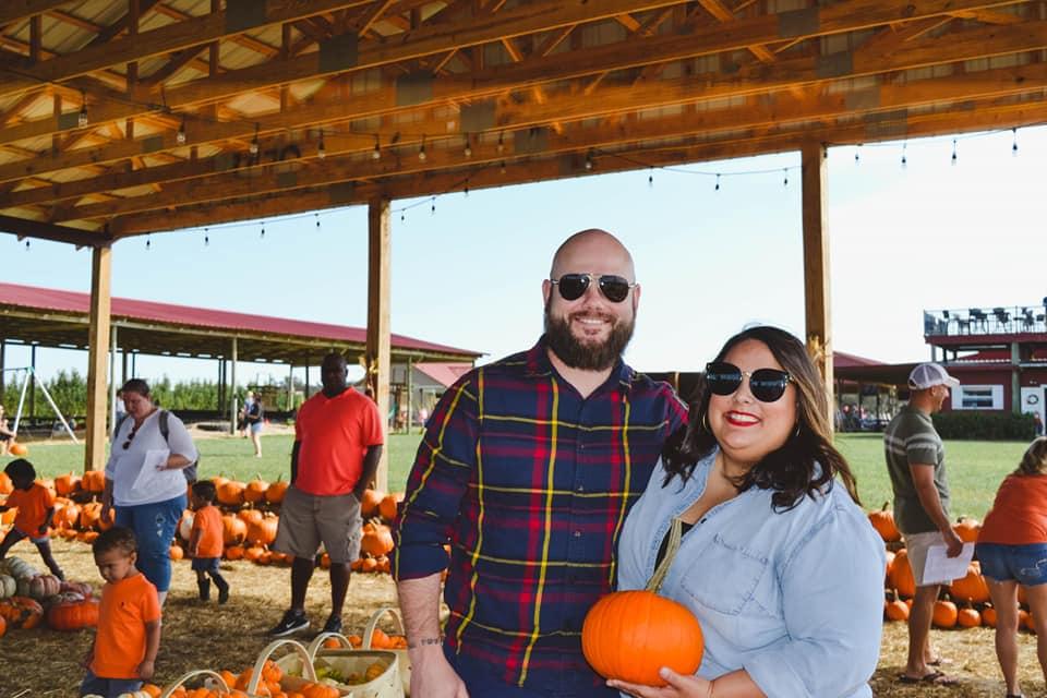 engaged couple pumpkin picking