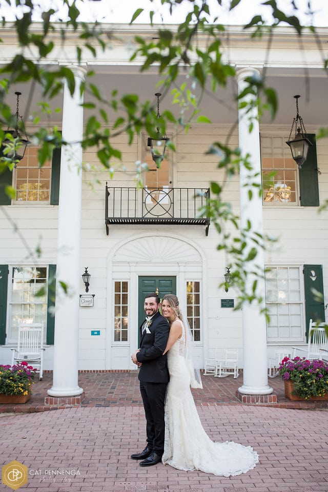 bride and groom standing outside of estate