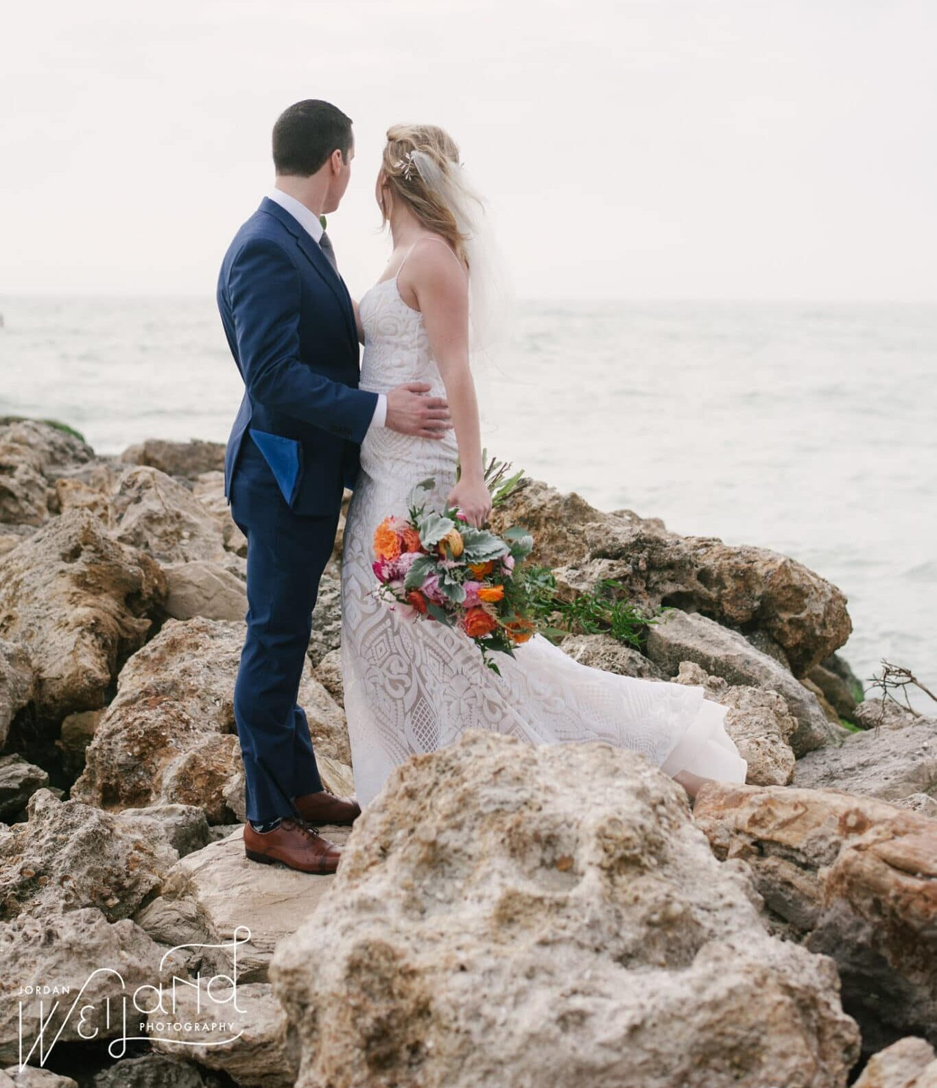 Kiss of Perfection, bride and groom standing on rocks overlooking water