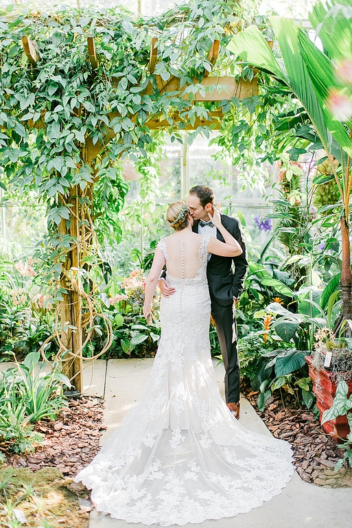 bride and groom kissing under trellis of greens