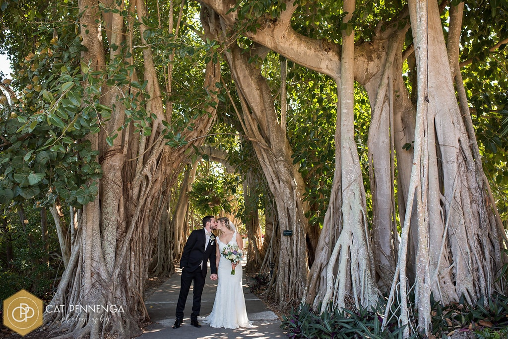bride and groom kissing under tall trees in the woods