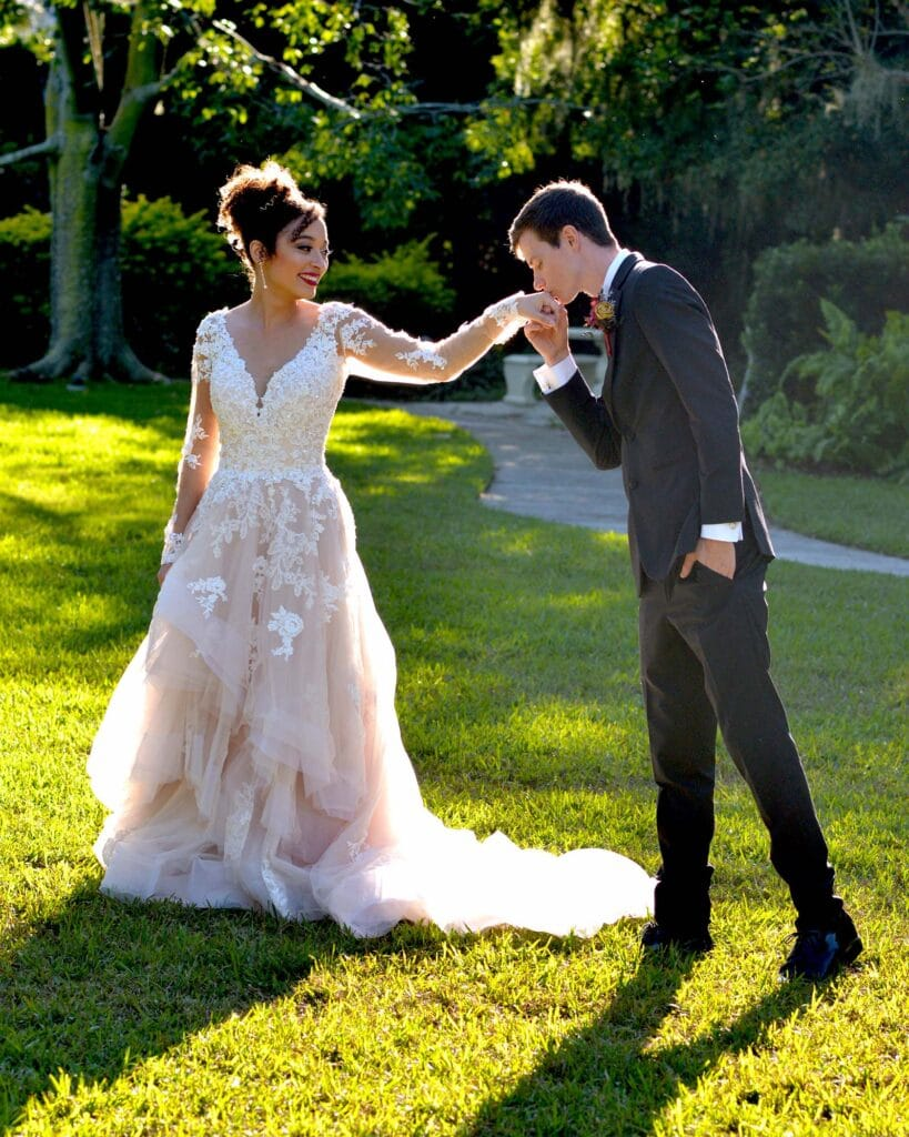 Nadine Nasby Photography, groom kissing bride's hand outside on grass