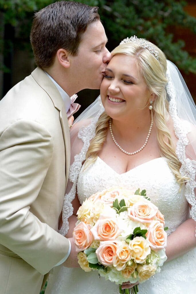 Nadine Nasby Photography, bride smiling and groom kissing her