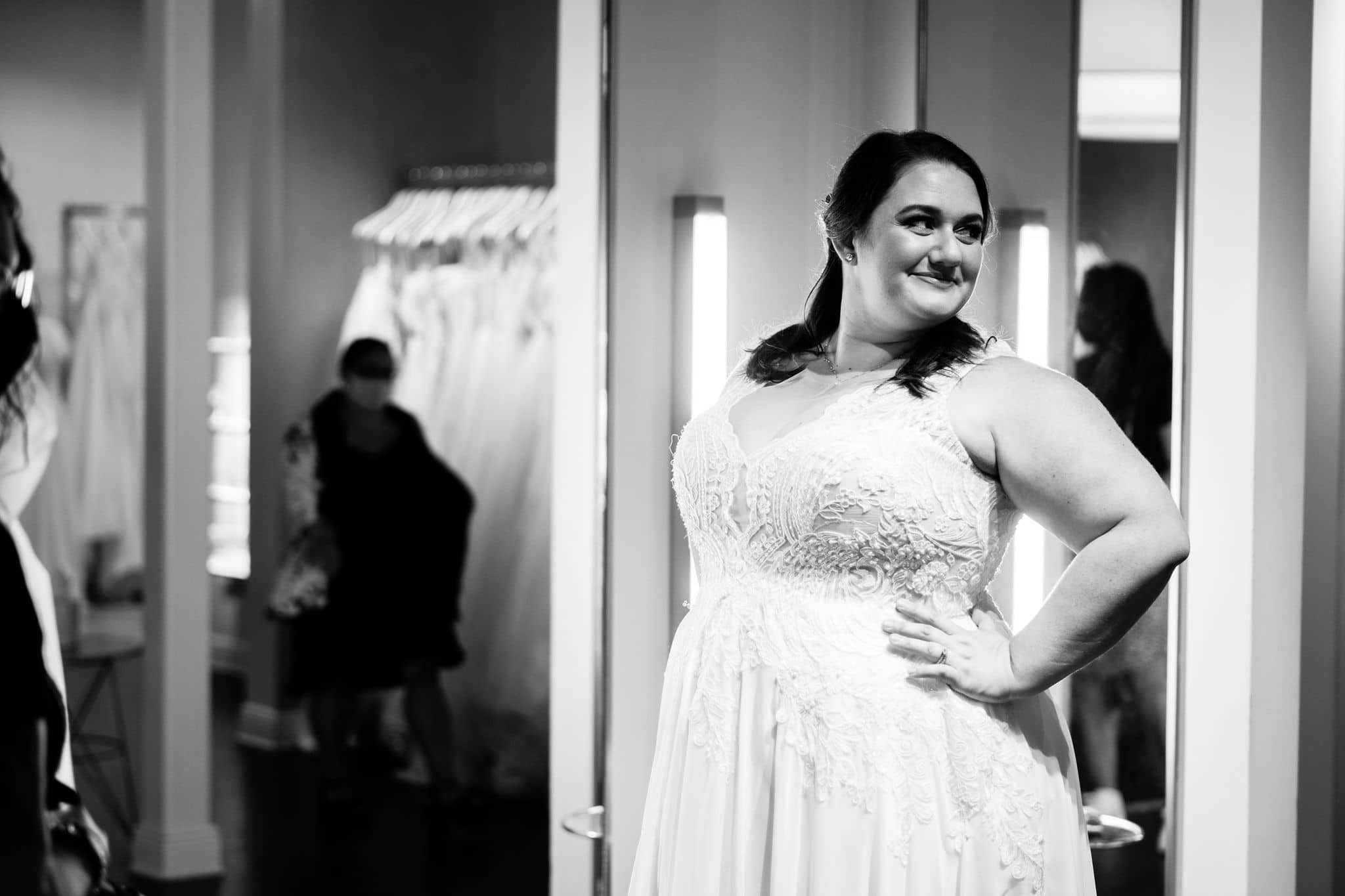 bride to be trying on plus size wedding dresses