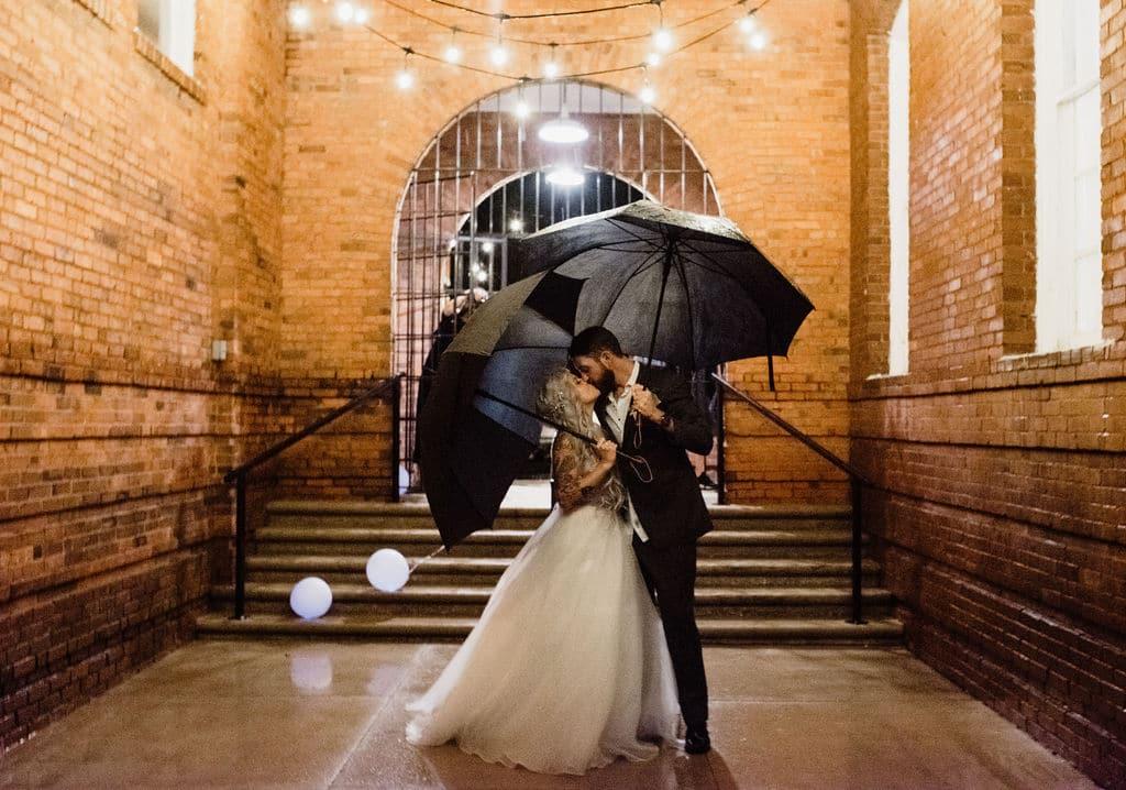 bride groom kissing outside under umbrellas