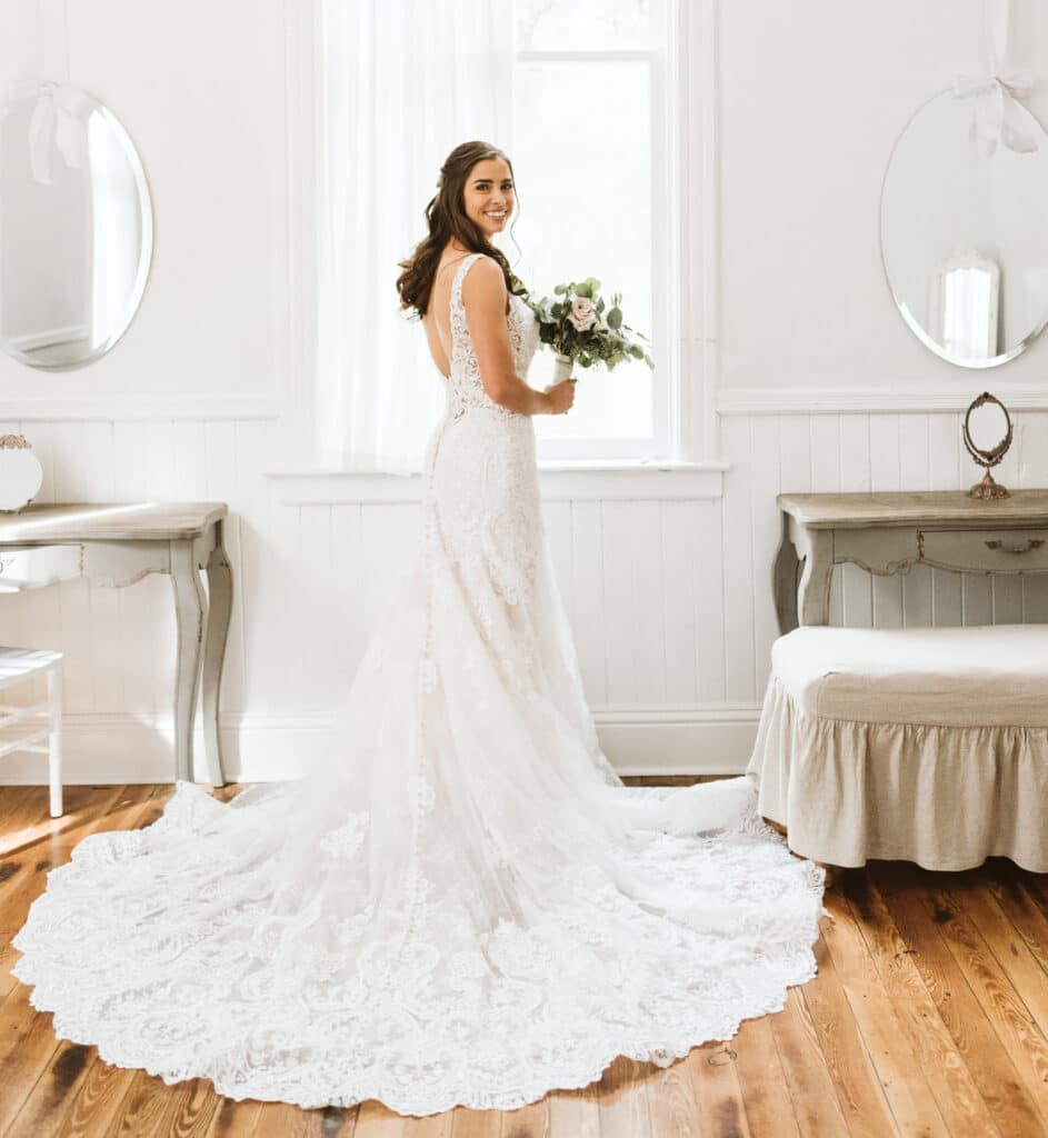 bride standing in front of window with bouquet