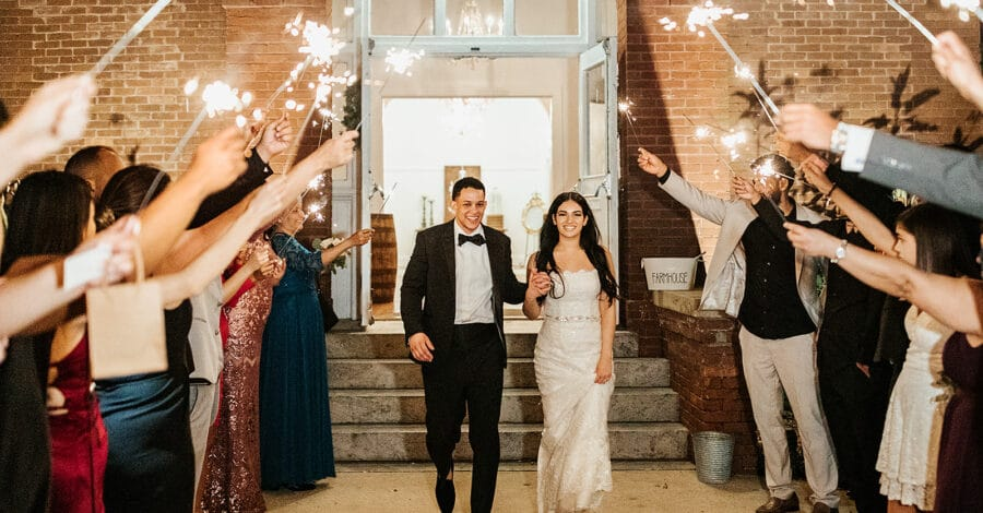 bride and groom walking outside with guest holding sparklers