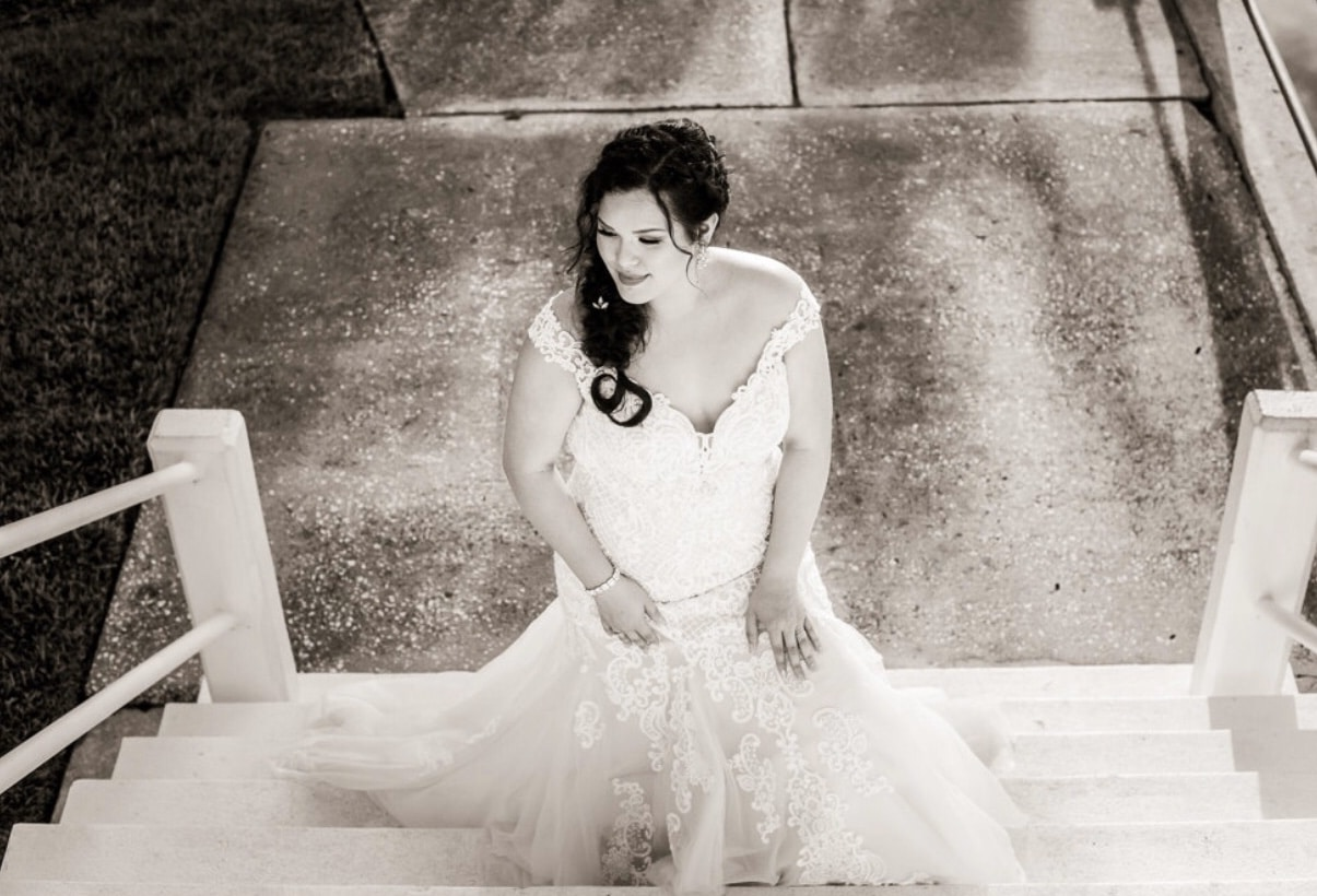 black and white photo looking down on bride on steps