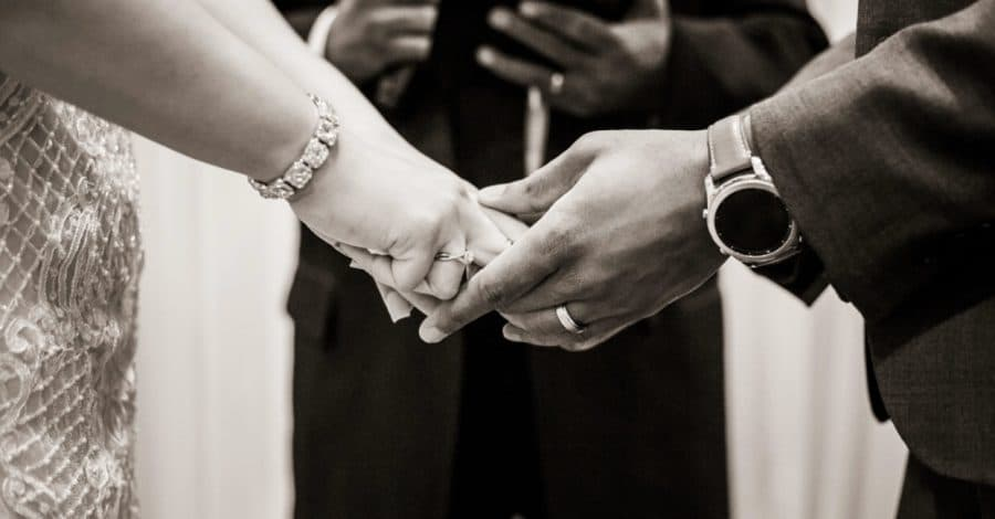 With This Ring, black & white close up of bride & groom holding hands in front of officiant