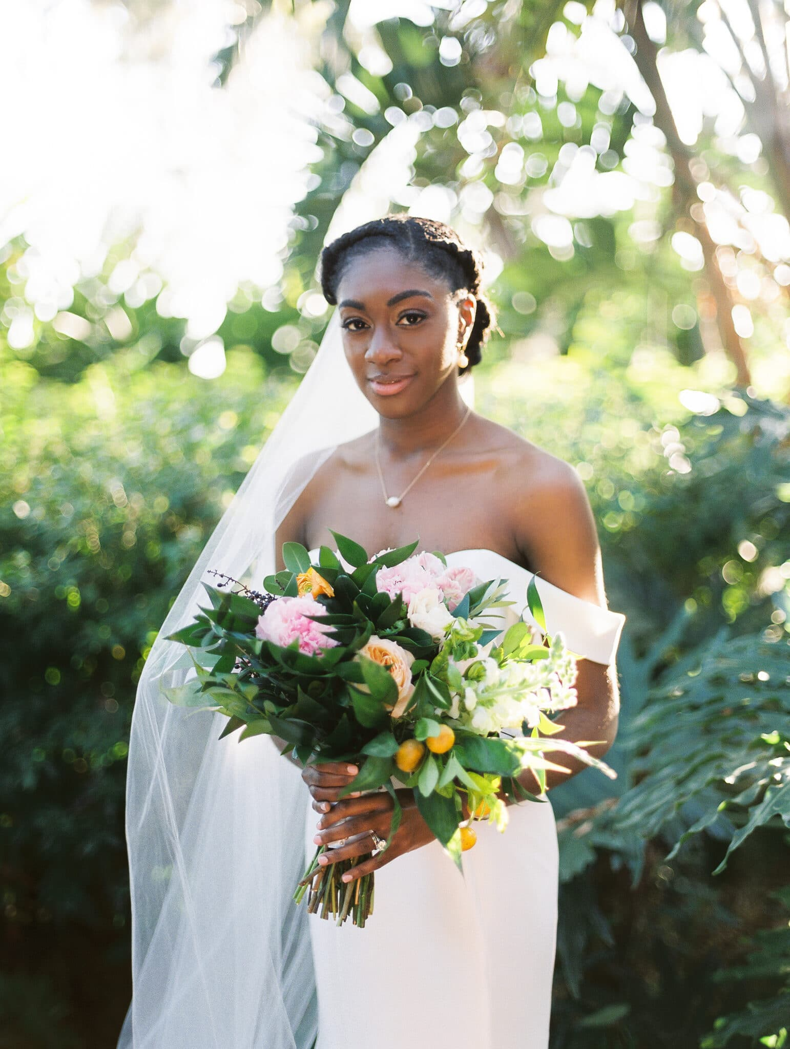 bride standing outside with bouquet