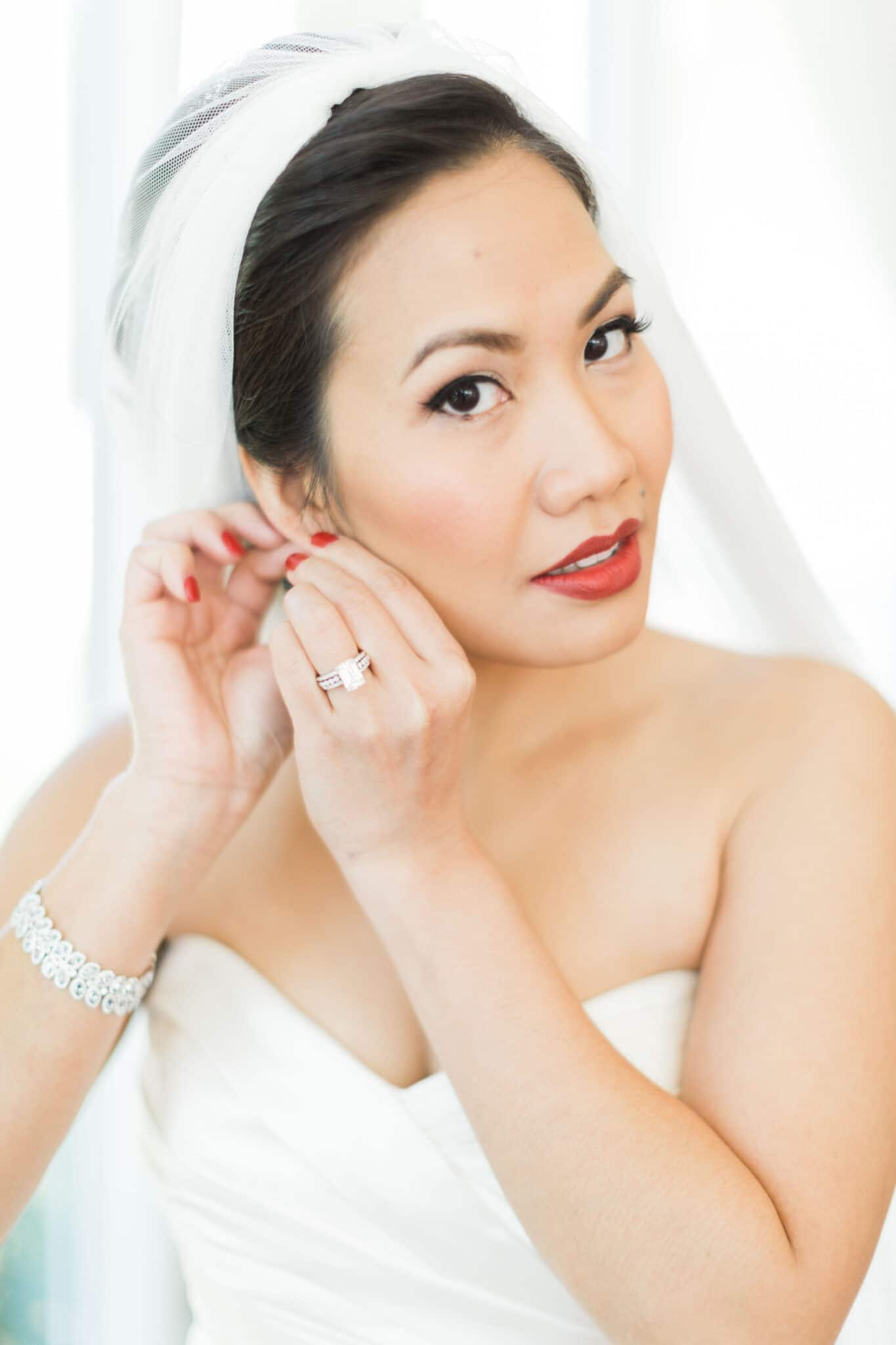 M3 Beauty, bride putting earrings on with make up ready