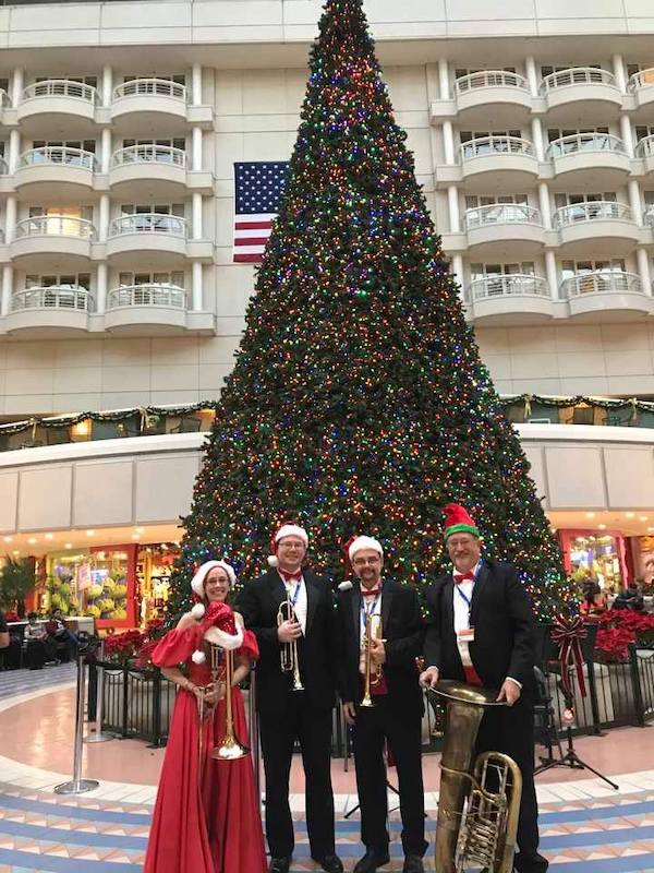 Music Remembrance holiday band standing in front of large christmas tree