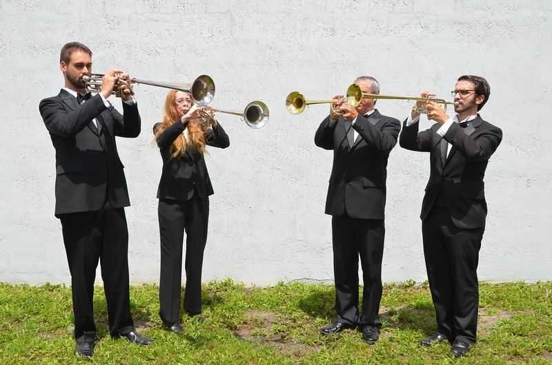Music Remembrance horn section performing outside near body of water