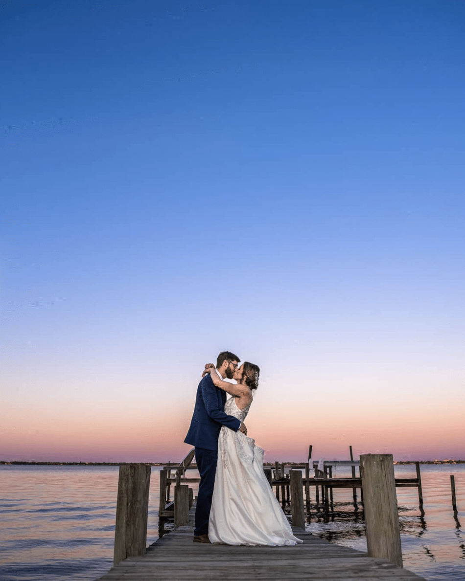 bride and groom at small wedding sunset on the water
