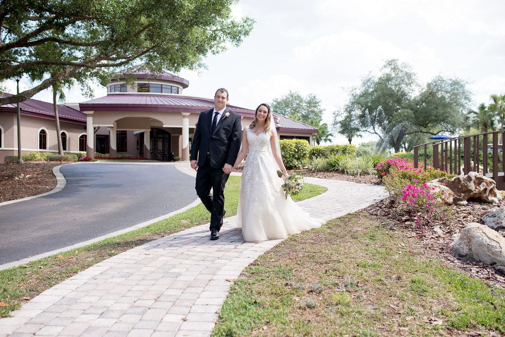 bride and groom walking down brick pathway on their wedding day, with a walking bride and beautiful flowers behind them