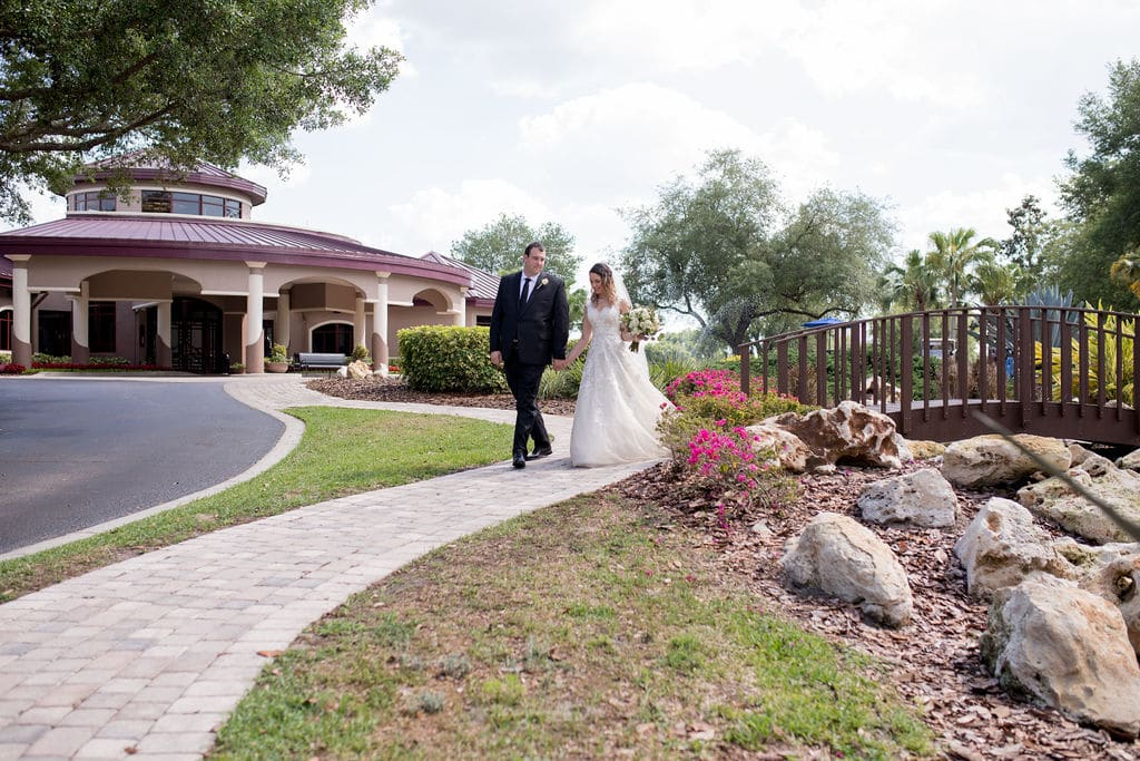 bride and groom walking down a brick pathway between beautiful flowers and decorative rocks next to a walking bride