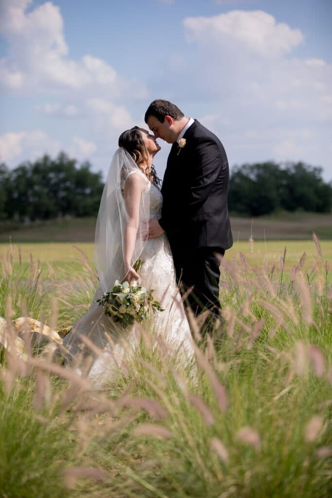 bride and groom standing nose to nose outside in a field with the groom holding his bride by her waist and the bride holding her bouquet down to her side