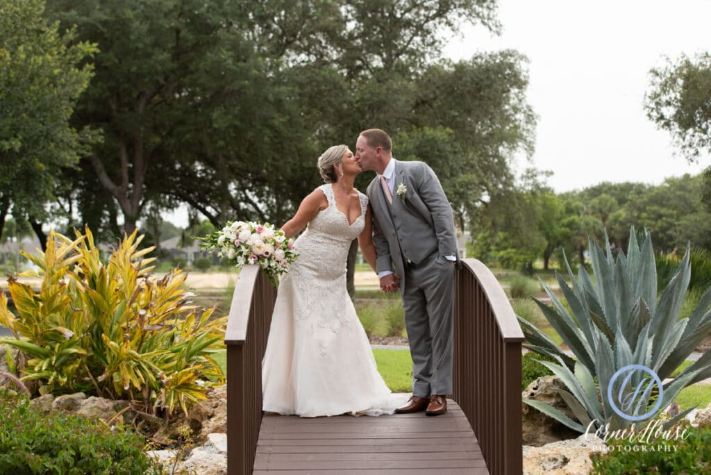 bride and groom kissing and holding hands while standing on small walking bride with beautiful flowers and plants on either side of them