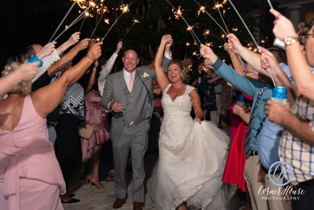bride and groom walking between all of their guests during a nighttime sparkler exit