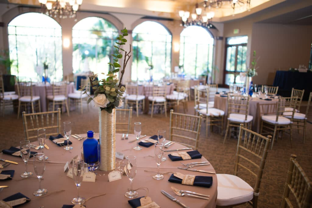 tables setup for wedding reception, with beautiful chairs, colorful linens, and flower centerpieces