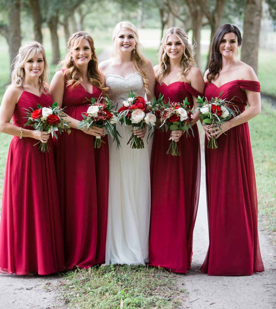 bride with bridesmaids in red, outside