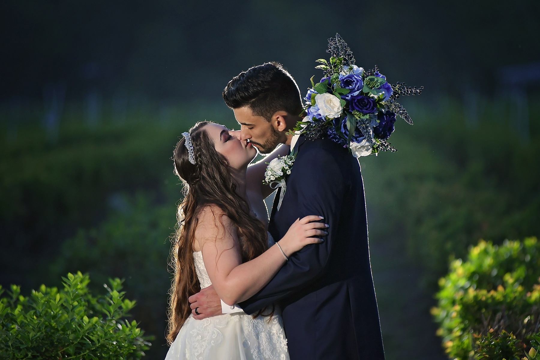 backlit photo bride and groom kissing holding wedding bouquet of blue and purple flowers