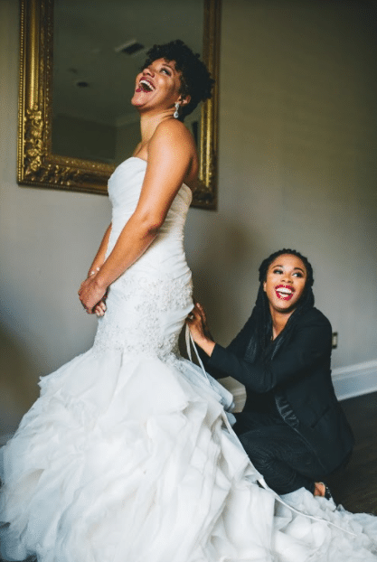 bride laughing while getting dress