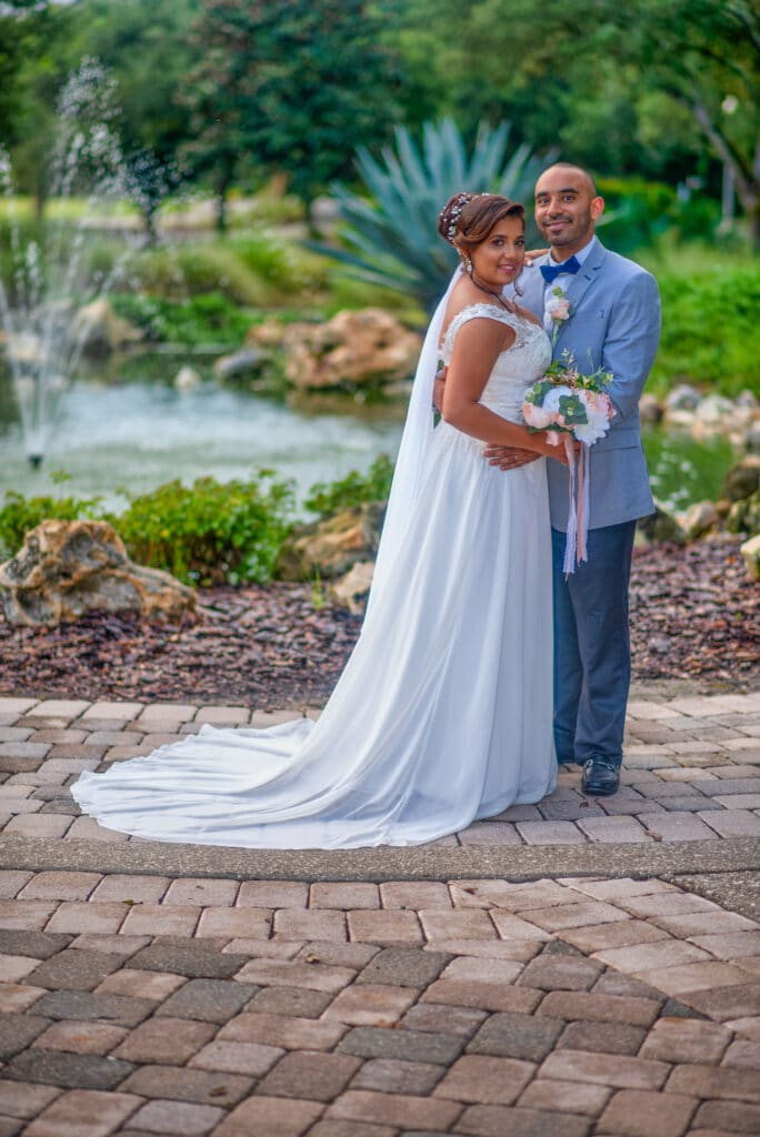 bride and groom standing on brick pathway outside with beautiful pond and fountain behind them