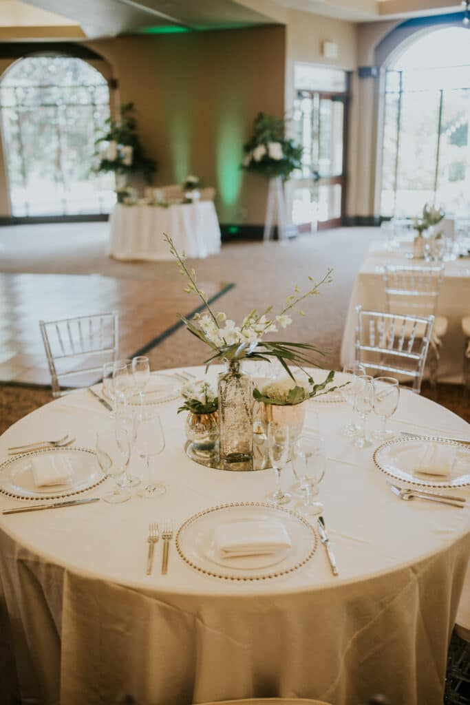 table setup for wedding reception, with gold linen and plates, flower centerpieces, and green uplights in background