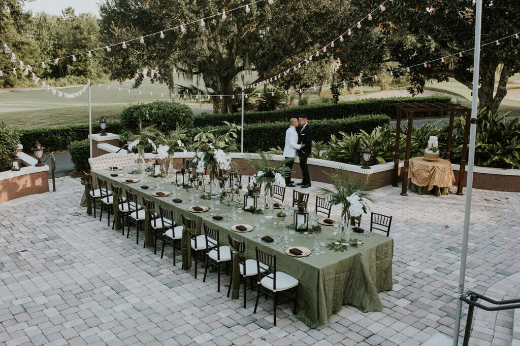 married couple kissing while standing under market lights on a brick courtyard setup for their reception, with one long table setup for guests