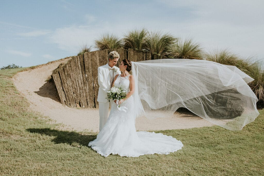 married couple standing on a golf course in front of a deep sand trap with a wood wall behind them