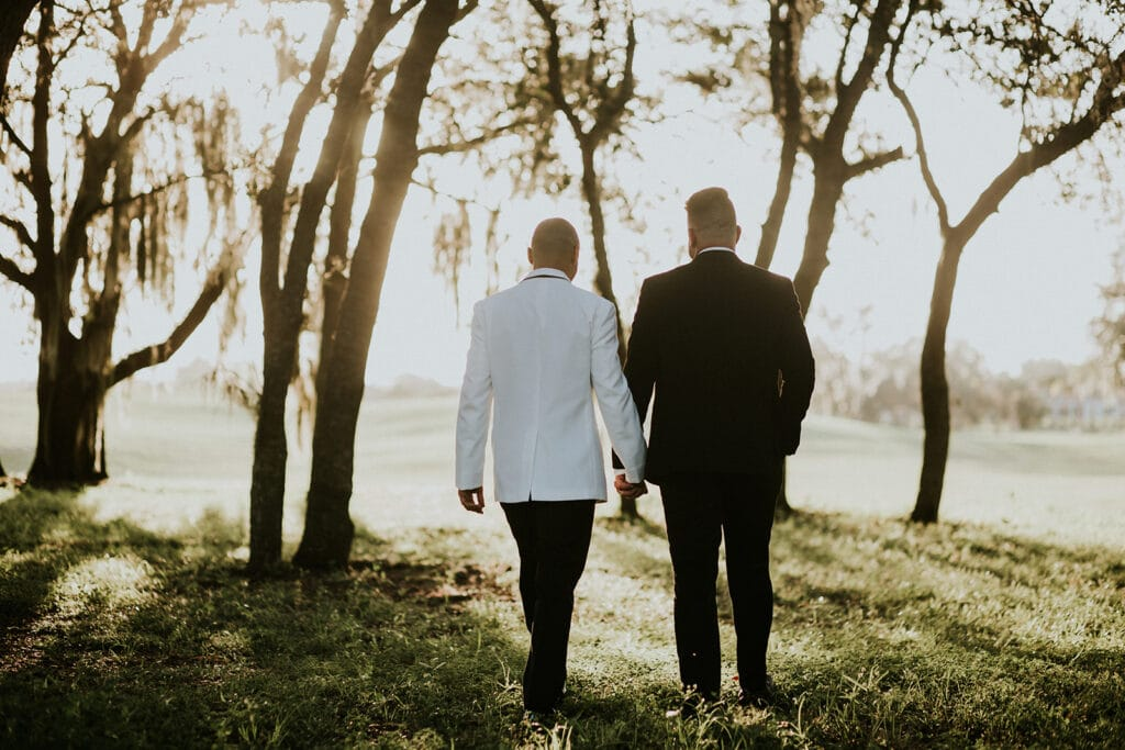 married couple walking through a group of trees as the sun shines down on them on their wedding day