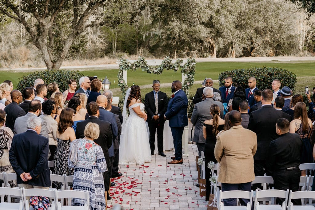 bride and groom with large bridal party standing in front of flower covered archway during outdoor wedding ceremony