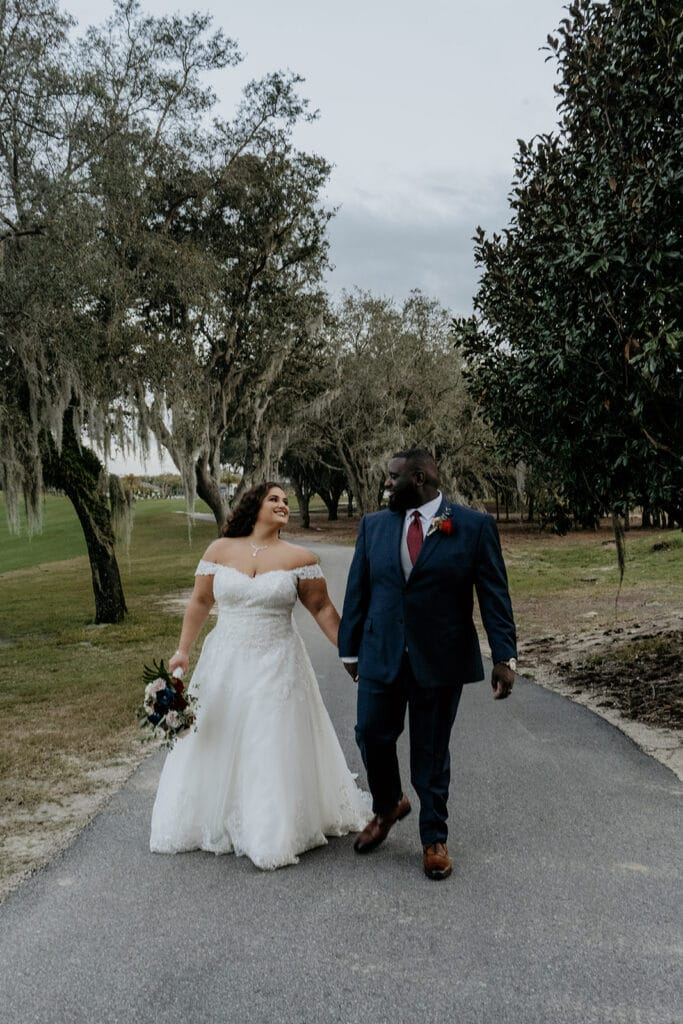 bride and groom walking down a paved pathway between beautiful trees covered in florida moss
