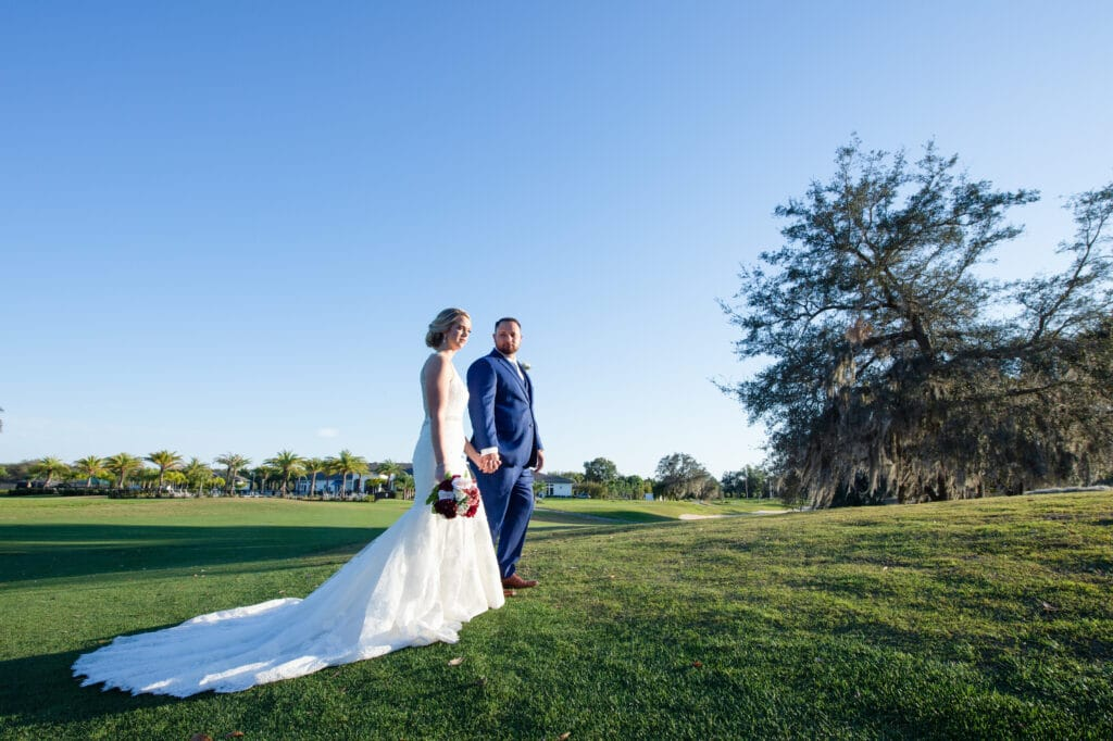 bride and groom walking through golf course on their wedding day