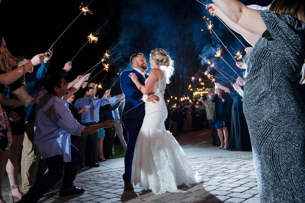 bride and groom embracing during sparkler exit from their wedding reception at night