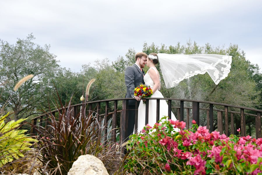 bride and groom standing with their foreheads pressed together, standing on a small walking bridge with beautiful colorful flowers in front of them