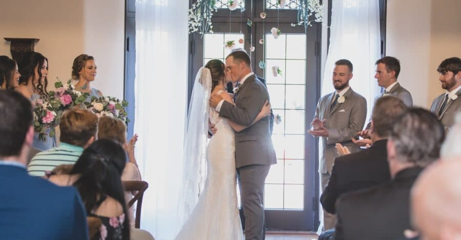 bride and groom kissing during their indoor wedding ceremony while their guests and bridal party cheer them on