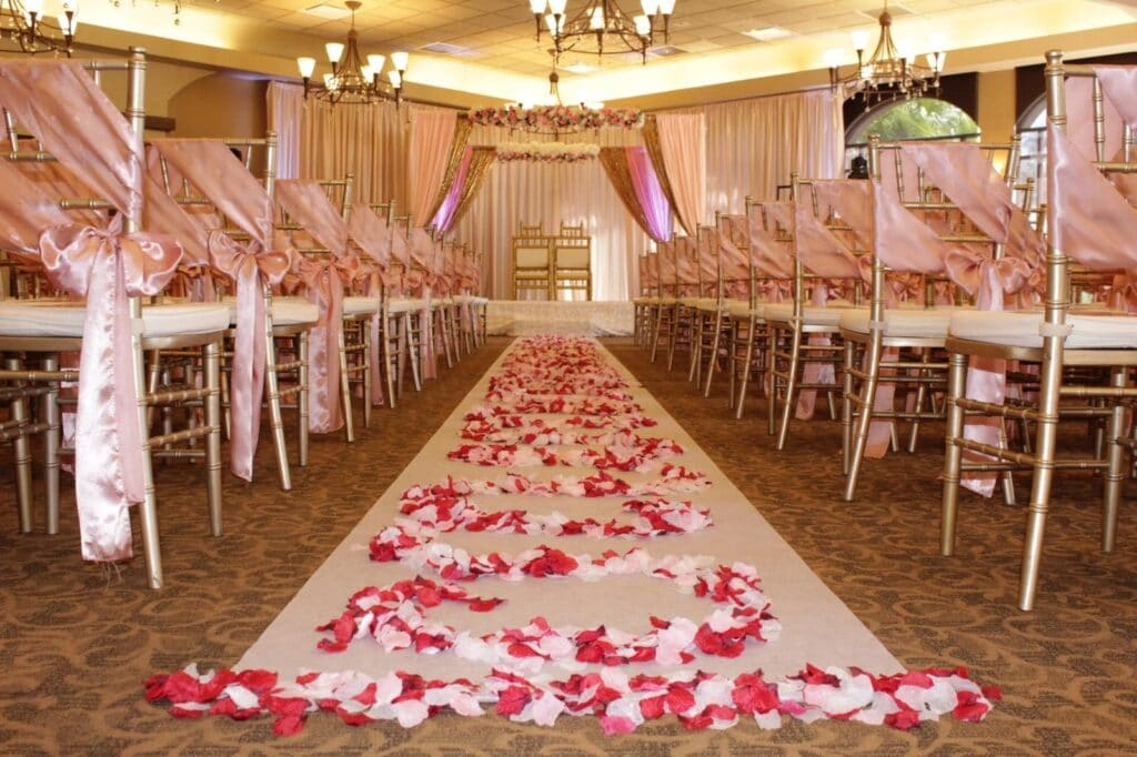 room decorated for indoor wedding ceremony, with red, pink, and white flower pedals, pink sashes on the chairs, beautiful chandeliers, and curtains