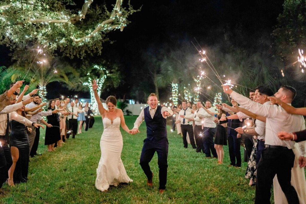 sparkler exit at night at The Grand Ol' Barn, with bride holding her hand up in the air in celebration and the groom pointing and laughing