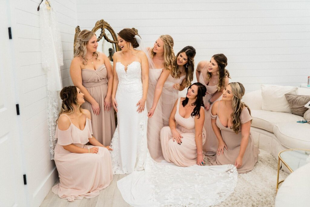 bride laughing while bridesmaids in their dresses help her get ready for her wedding at The Grand Ol' Barn