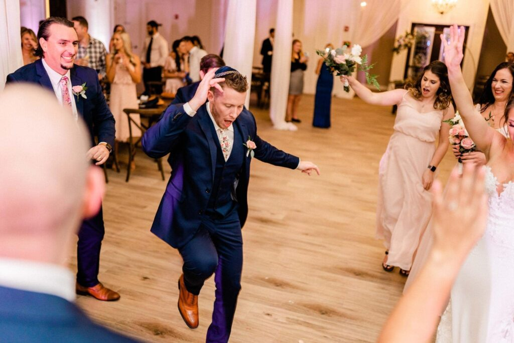 groom dancing alone in middle of dance floor while guests and bridal party cheer him on at The Grand Ol' Barn