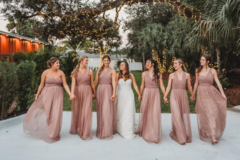 bride and her bridesmaids laughing and holding hands while outside at The Grand Ol' Barn standing underneath an old tree wrapped in white lights